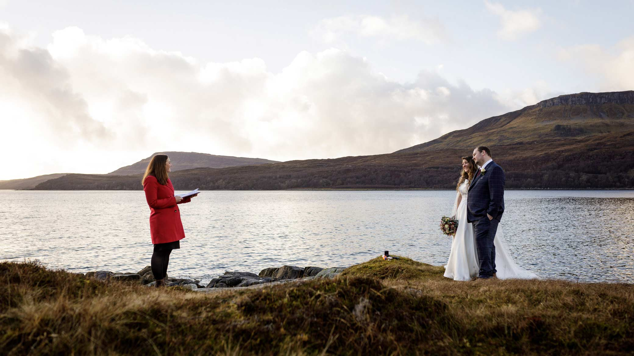 A man and woman marry in front of a loch