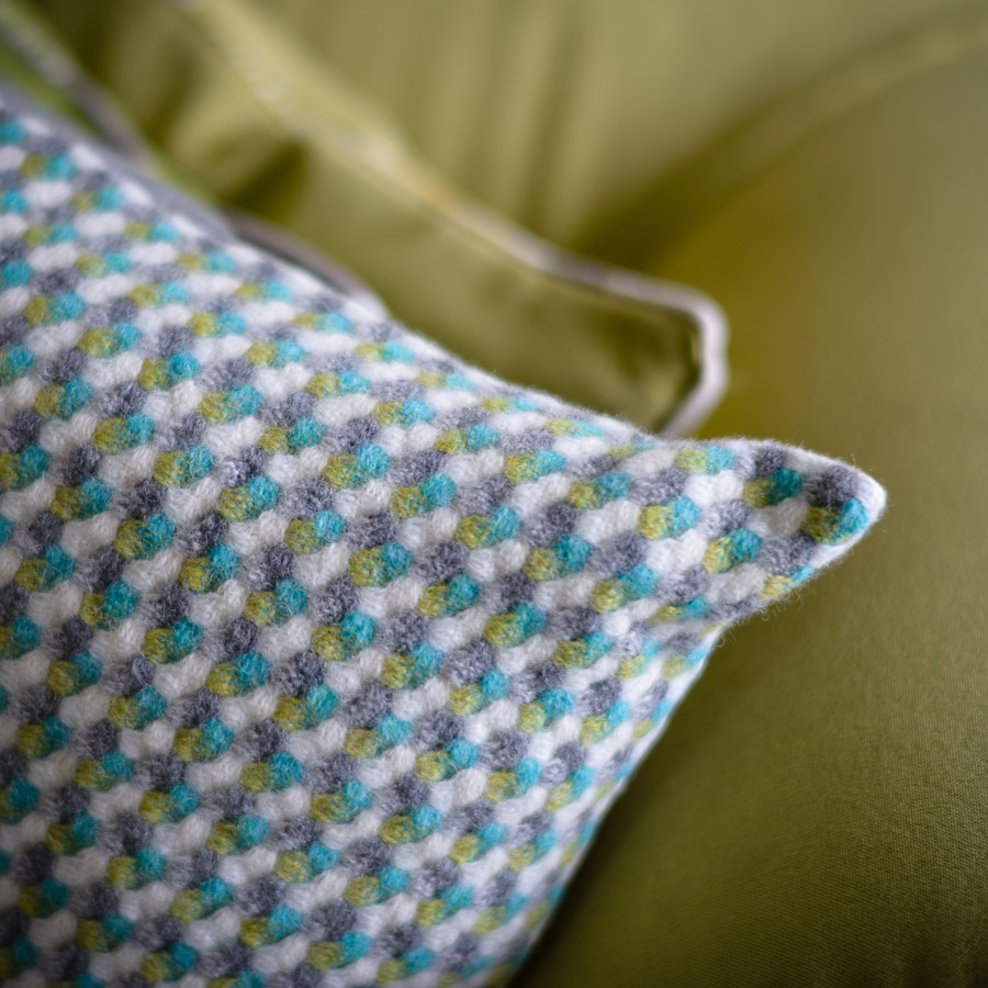 Detail of white, grey, blue and green woven cushion by weaver Maggie Williams