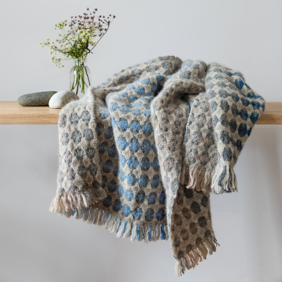 Woven throw in blue and grey by weaver Maggie Williams on shelf with vase of flowers