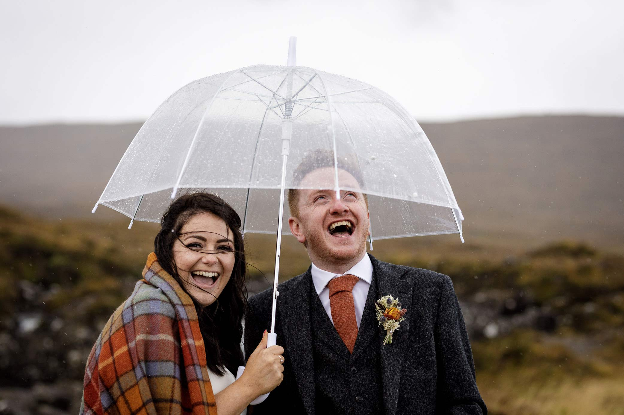 Man and woman smiling under an umbrella