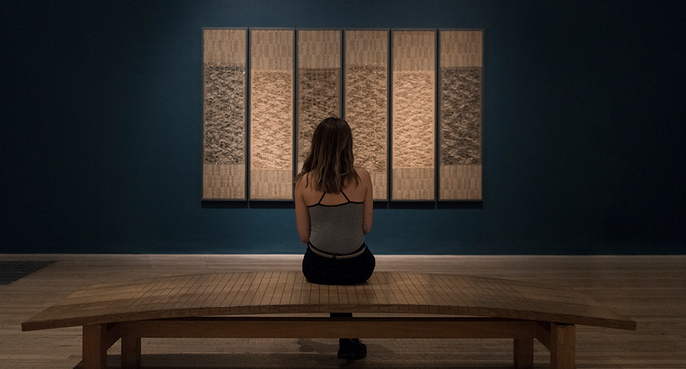 Woman looking at Anni Albers wall hanging