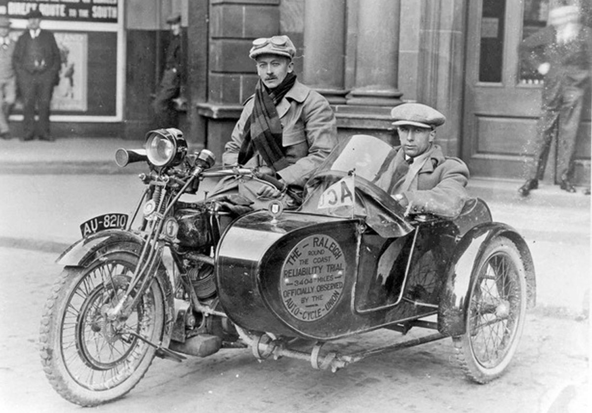 Black and white photograph of a man on a Raleigh motorcycle and another in a sidecar, from the 1920s. Both appear to be wearing tweed caps.
