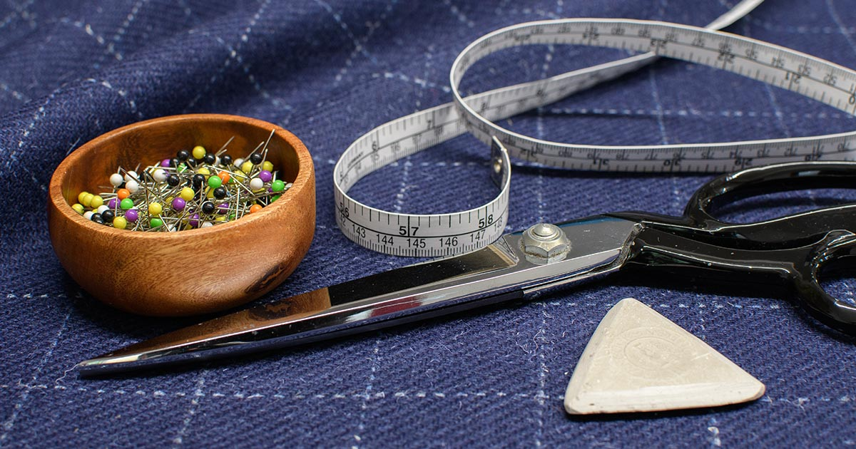 tape measure, pins and scissors on tweed