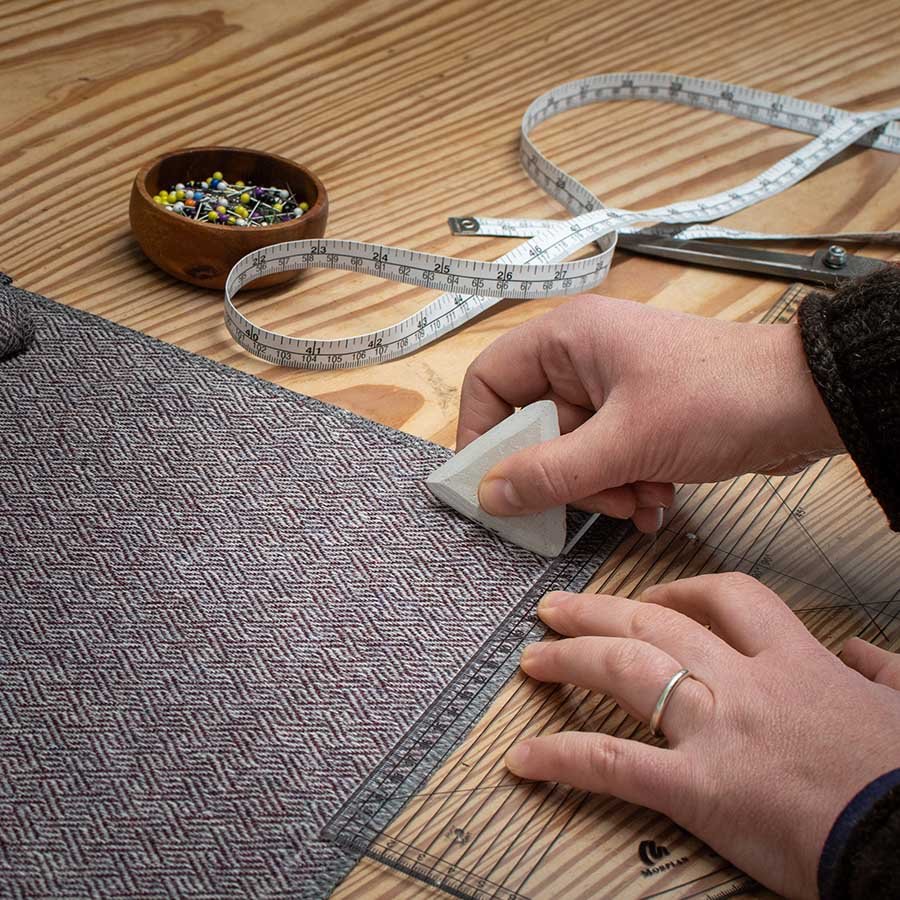 hands marking tweed fabric with tailors chalk