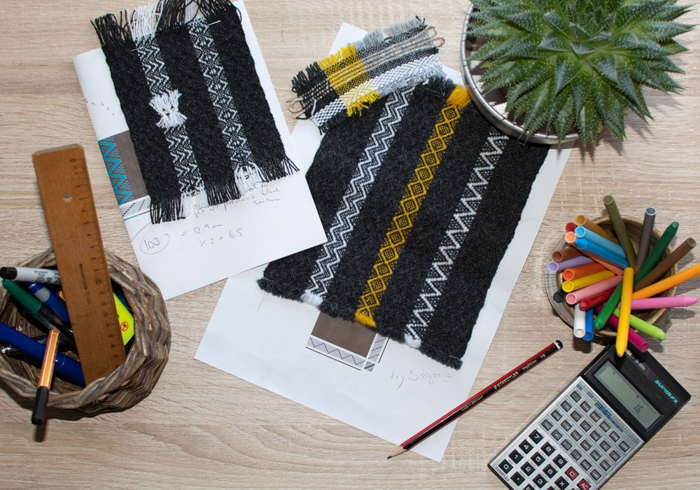 samples of weaving and calculator on a table
