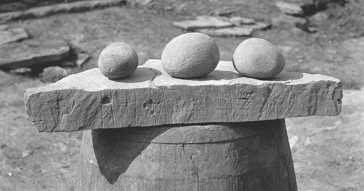 Carved neolithic stone with 3 pebbles on it